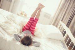 Niño que hace ejercicios mientras que miente en cama Fotos de archivo libres de regalías