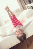 Niño que hace ejercicios mientras que miente en cama Foto de archivo libre de regalías
