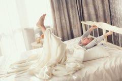 Niño que hace ejercicios mientras que miente en cama Imagen de archivo