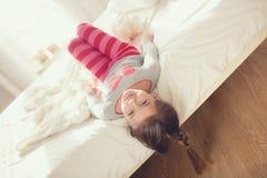 Niño que hace ejercicios mientras que miente en cama Foto de archivo