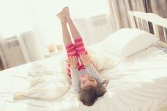 Niño que hace ejercicios mientras que miente en cama Imagen de archivo libre de regalías