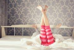 Niño que hace ejercicios mientras que miente en cama Imagenes de archivo