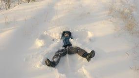 Niño que hace el ángel de la nieve que se acuesta en nieve metrajes