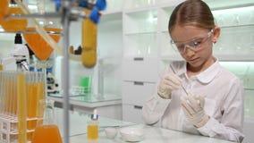 Niño que hace el experimento químico en el laboratorio de la escuela, estudiante Girl en clase de la ciencia imagen de archivo libre de regalías