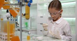 Niño que hace el experimento químico en el laboratorio de la escuela, estudiante Girl en la clase 4K de la ciencia almacen de metraje de vídeo