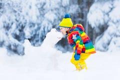 Niño que hace el muñeco de nieve Juego de los niños en nieve en invierno imagen de archivo