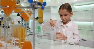 Niño que hace experimentos químicos en el laboratorio de la escuela, estudiante Girl Chemistry Class del niño almacen de metraje de vídeo
