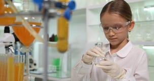 Niño que hace experimentos químicos en el laboratorio de la escuela, estudiante Girl Chemistry Class 4K almacen de metraje de vídeo