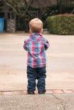 Niño que hace frente al exterior ausente con un parque en el fondo Imagenes de archivo