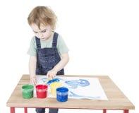 Niño que hace la pintura en el pequeño escritorio fotografía de archivo libre de regalías