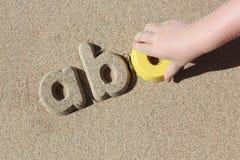 Niño que hace letras de la arena en la playa Imagen de archivo libre de regalías