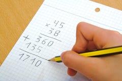 Niño que hace una multiplicación de la matemáticas en la escuela Foto de archivo libre de regalías