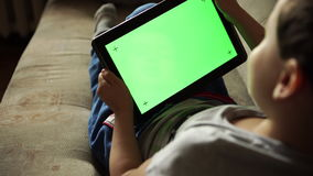 Niño que inclina a los left and right una tableta con la pantalla verde, visión trasera almacen de metraje de vídeo