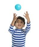Niño que intenta coger una bola Fotografía de archivo libre de regalías