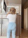 Niño que intenta girar microonda Fotografía de archivo libre de regalías