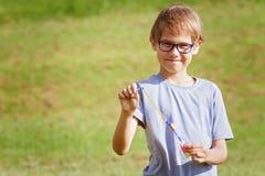 Niño que juega al aire libre en un parque con el juguete elástico del cohete del helicóptero de la flecha Imagen de archivo
