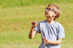 Niño que juega al aire libre en un parque con el juguete elástico del cohete del helicóptero de la flecha Fotos de archivo libres de regalías