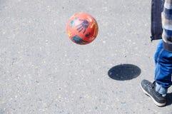 Niño que juega al fútbol en el asfalto, salto de la bola, jugador de equipo de fútbol, entrenando a forma de vida al aire libre,  Fotos de archivo