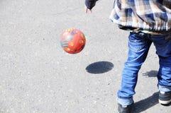 Niño que juega al fútbol en el asfalto, salto de la bola, jugador de equipo de fútbol, entrenando a forma de vida al aire libre,  Foto de archivo libre de regalías