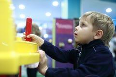 Niño que juega al juego de arcada foto de archivo