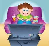 Niño que juega al videojuego en el sofá Fotografía de archivo