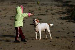 Niño que juega alcance con su perro en la playa Imágenes de archivo libres de regalías