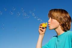 Niño que juega burbujas que soplan Imagen de archivo libre de regalías