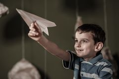 Niño que juega con el avión de papel Foto de archivo libre de regalías