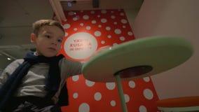 Niño que juega con el disco giratorio en la exposición de Yayoi Kusama metrajes