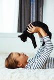 Niño que juega con el gatito Foto de archivo