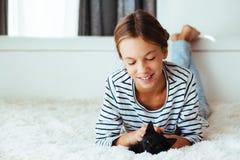 Niño que juega con el gatito Fotos de archivo
