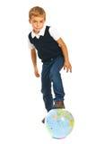 Niño que juega con el globo del mundo Foto de archivo libre de regalías