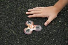 Niño que juega con el hilandero en el patio Fotos de archivo libres de regalías