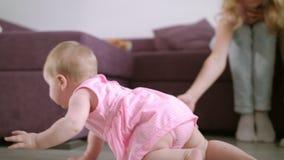 Niño que juega con el juguete en piso El bebé dulce goza el caminar en sitio almacen de metraje de vídeo