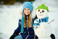 Niño que juega con el muñeco de nieve Fotografía de archivo libre de regalías