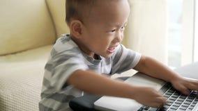 Niño que juega con el ordenador portátil metrajes