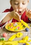 Niño que juega con el plato de los espaguetis hecho con plasticine imagen de archivo libre de regalías