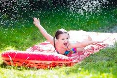 Niño que juega con el tobogán acuático del jardín Fotos de archivo libres de regalías