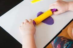 Niño que juega con la arcilla colorida que moldea diversas formas imagen de archivo libre de regalías