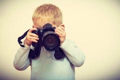 Niño que juega con la cámara digital profesional grande Foto de archivo
