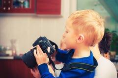 Niño que juega con la cámara digital profesional grande imagen de archivo