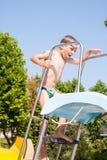 Niño que juega con la diapositiva en la piscina Fotos de archivo libres de regalías