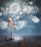Niño que juega con la luna y las estrellas en la noche