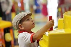 Niño que juega con la máquina de juego Imágenes de archivo libres de regalías