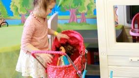 Niño que juega con la muñeca en el patio Juegos del bebé en los juegos para los niños Juego de la hija de la madre almacen de metraje de vídeo