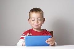 Niño que juega con la tablilla Fotografía de archivo libre de regalías
