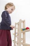 Niño que juega con la trayectoria de madera de la bola fotografía de archivo