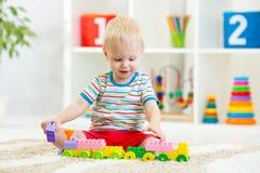 Niño que juega con las unidades de creación en la guardería Imagenes de archivo