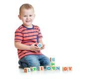 Niño que juega con los bloques de la letra aislados Fotos de archivo libres de regalías