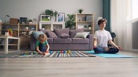 Niño que juega con los bloques en piso mientras que su mamá que medita en la posición de loto metrajes